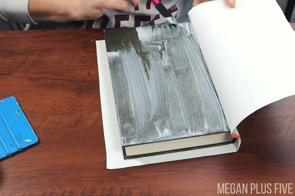 woman is painting matte finish mod podge onto the hardcover of the front of a book to make a DIY book stack. She is gluing floral printed paper to the book.