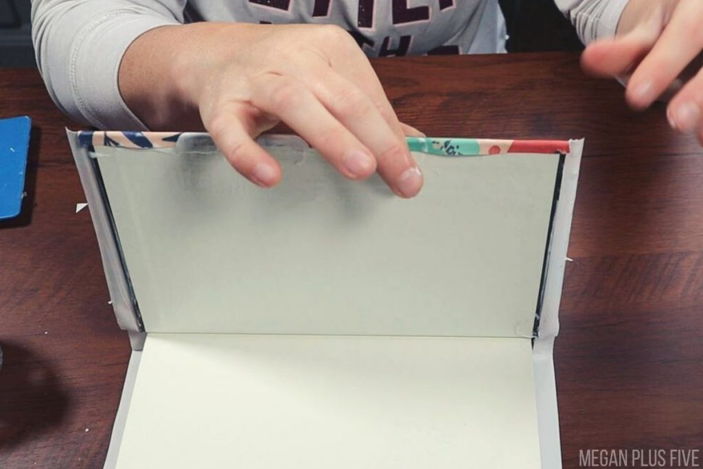 woman is gluing floral printed paper to a hardcover book. She is folding over the edges of the paper to cover the sides of the book.