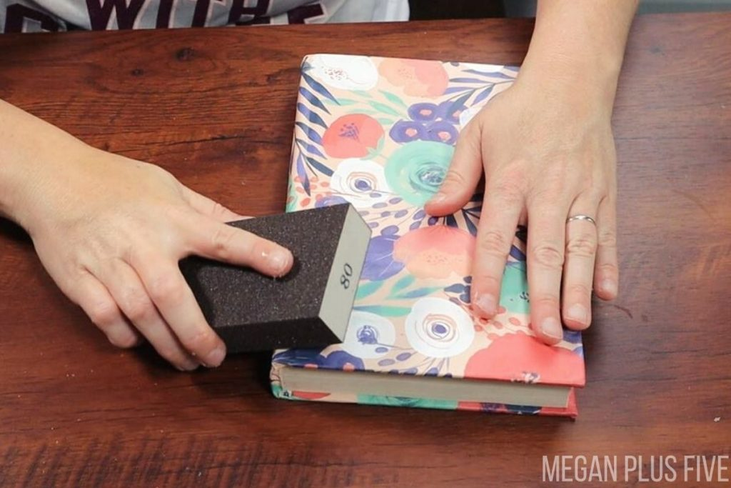 woman is using a sanding sponge to distress a floral print covered book stack.