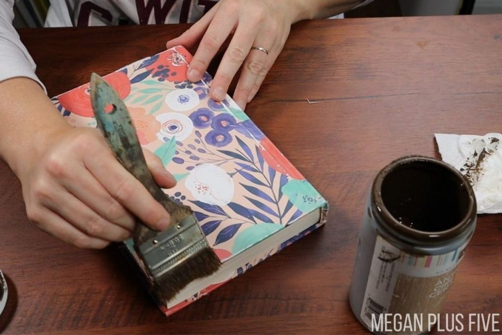 woman is using a chip brush and antique wax to distress a DIY book stack. Book is covered in floral printed gift bag paper. She is using a wide chip brush to apply the dark wax and dabbing it off on a paper towel as she goes.