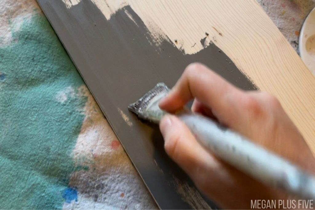 using a wide paintbrush to paint a wooden growth chart dark gray.