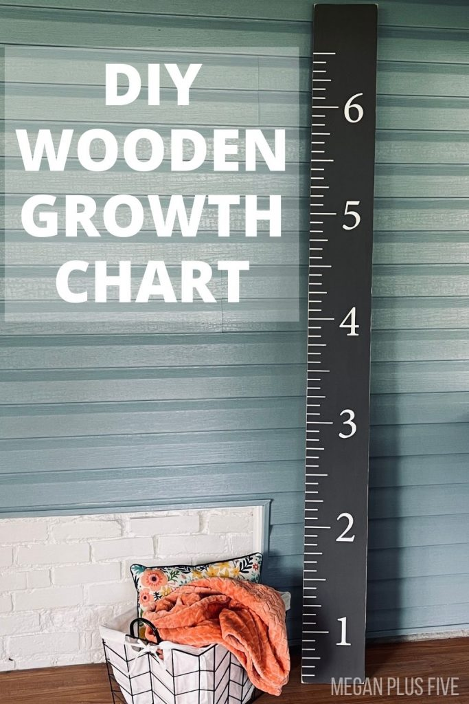 gray and white wooden growth chart ruler leaning against a blue wall. Wire basket with an orange blanket and floral pillow are on the ground next to the wood ruler chart.