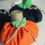 orange and black diy fabric pumpkins. Orange fabric pumpkin has a cork wrapped twine stem, twine / jute small bow and green felt leaves. There are 2 black fabric pumpkins behind the orange pumpkin. Fall pumpkin decorations are sitting on a white table.