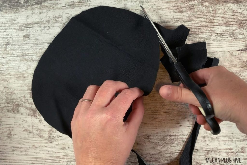 using scissors to cut a circle out of black fabric to make a fabric pumpkin for DIY fall decor