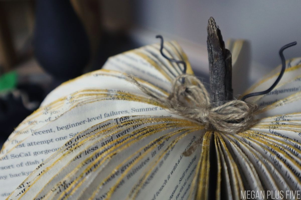 DIY book pumpkin craft. Book pages have been cut into the shape of a pumpkin. Outer edges of book pages are painted in a fall mustard yellow. There is a stick for the stem of the pumpkin and rustic curly wire pieces. There is a twine jute bow in the center of the pumpkin glued to the stem.