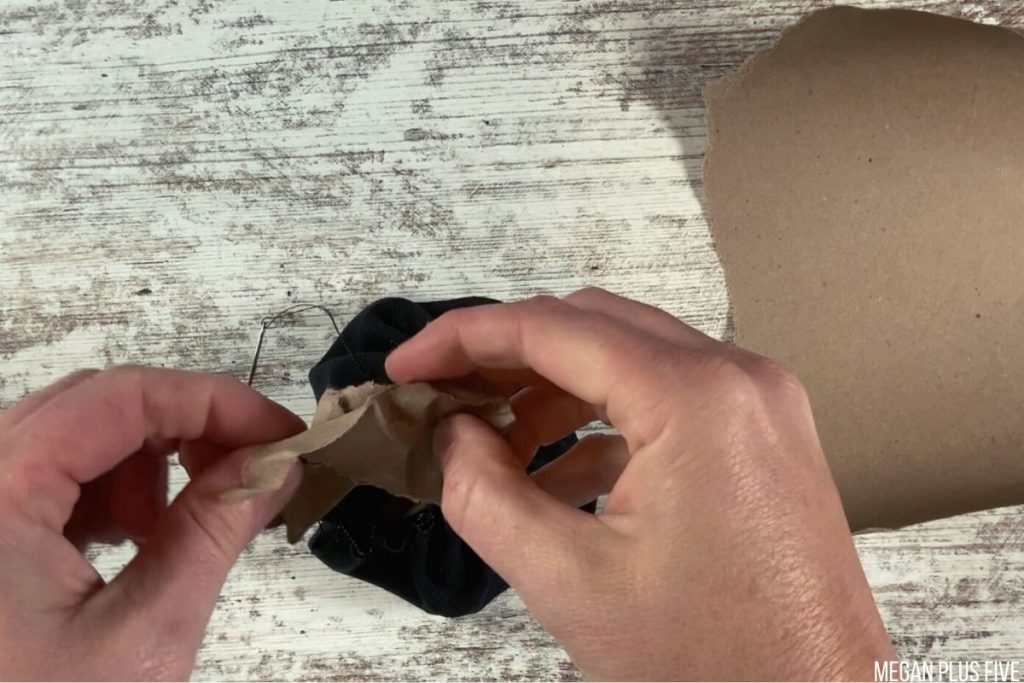 stuffing a black fabric pumpkin with brown craft paper