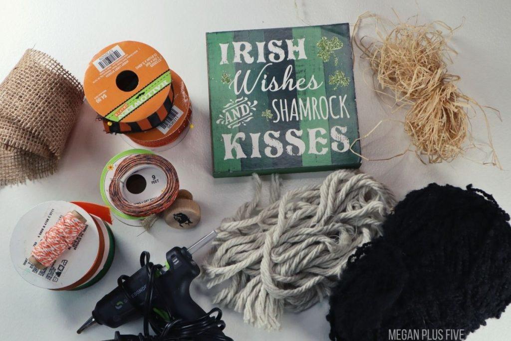 supplies and materials needed to make a DIY pumpkin craft using dollar tree things. Green St. Patrick's Day sign, black yarn, Halloween and fall colored ribbon, hot glue gun, mop head, raffia, burlap