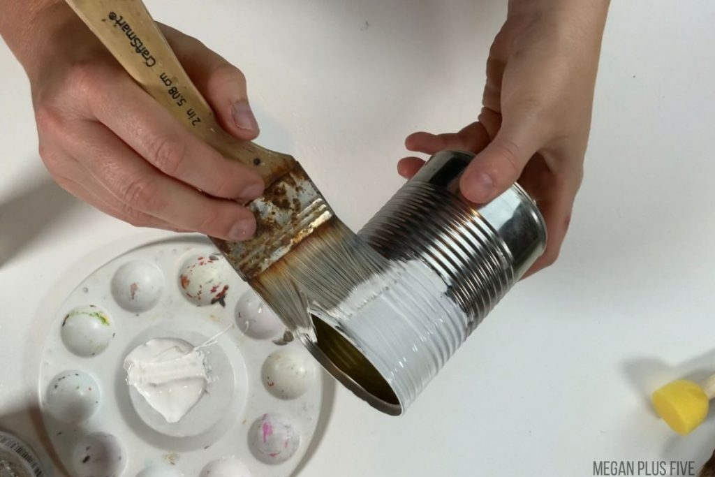 using a paintbrush to paint the outside of a metal tin can white to make a pumpkin craft