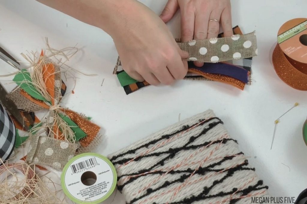 woman is overlapping fall and Halloween colored ribbons and burlap to make a simple bow for the top of a pumpkin