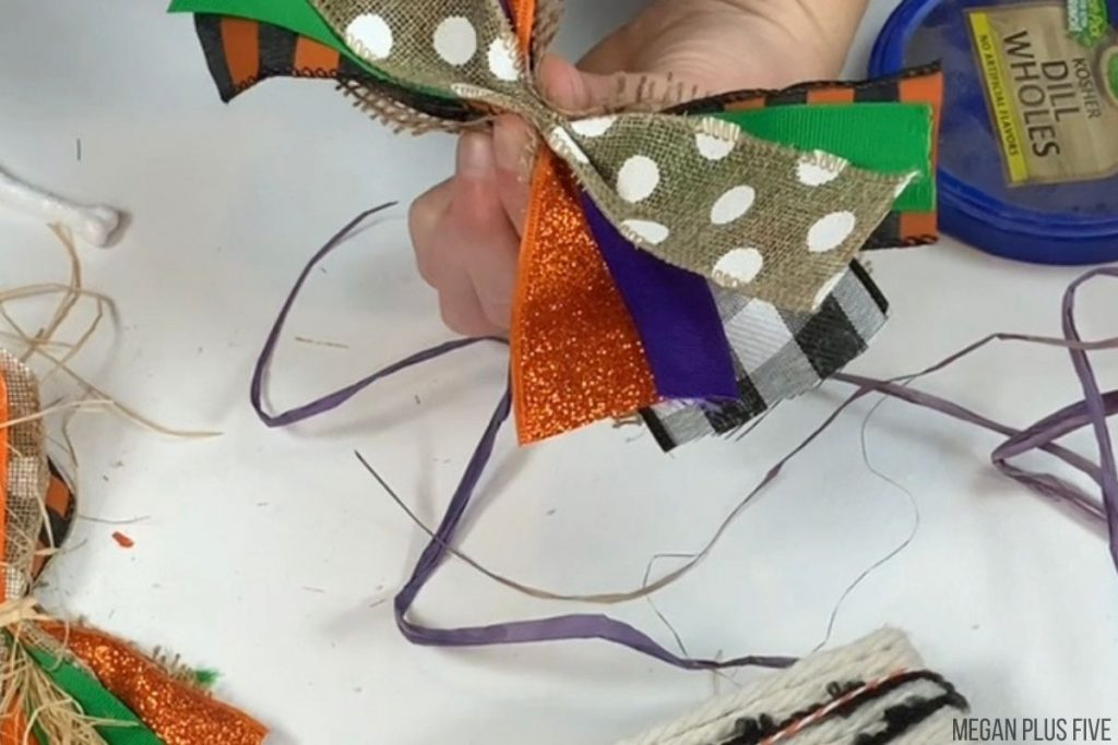 woman is making a simple bow from stirps of fall and Halloween colored ribbon. She has them overlapping and the middle pinched then wrapping twine around the center.