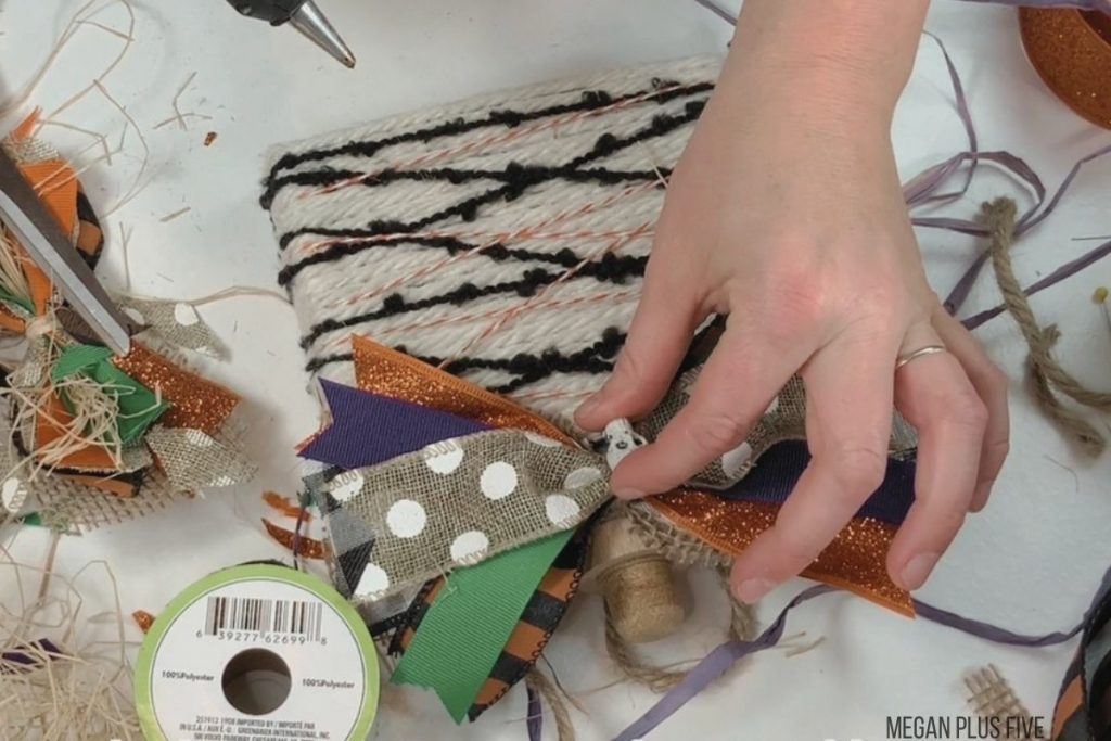 hot gluing a fall and Halloween colored bow to the front of a DIY pumpkins craft. Woman is attaching a skeleton accent to the front of the orange, green, purple bow