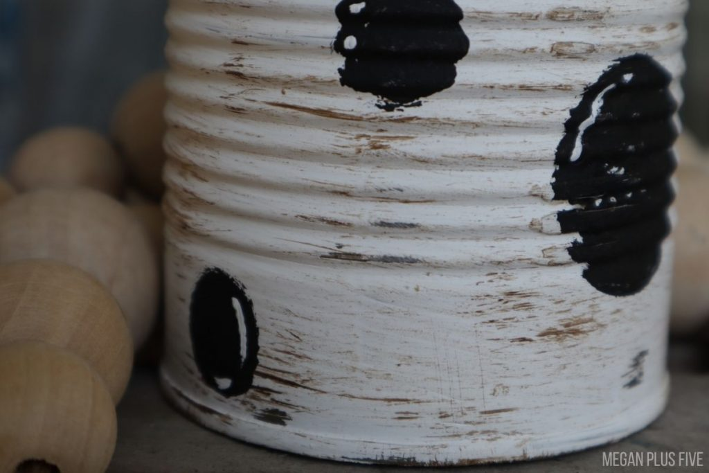 distress white painted tin can with black polka dots painted on it