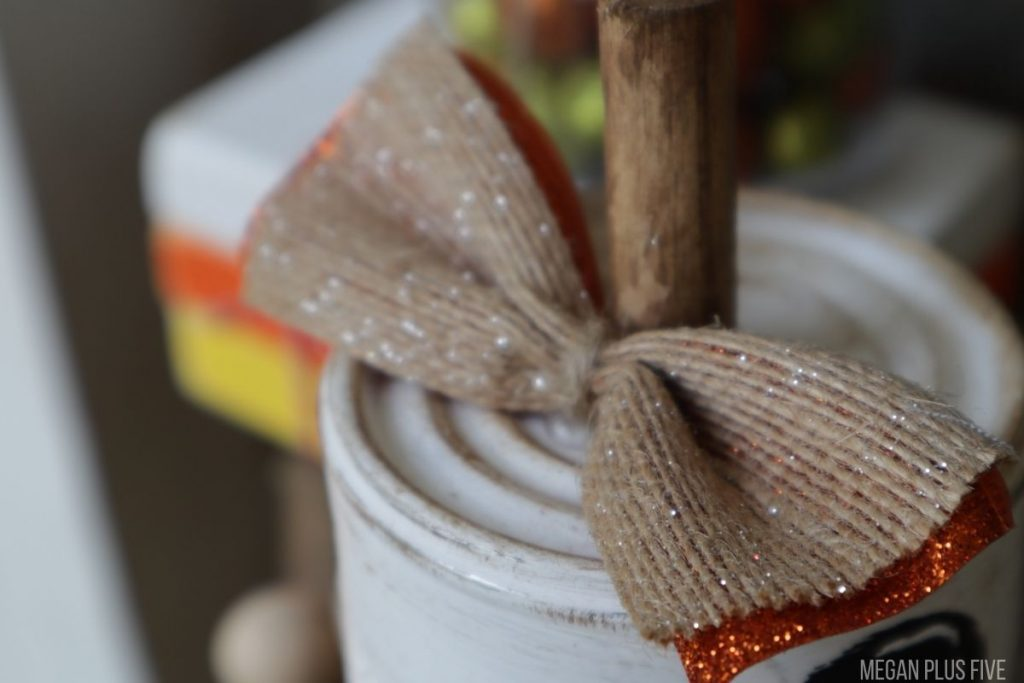 easy pumpkin made from a tin can, dowel rod stem with a burlap and orange glittery bow tied with twine.