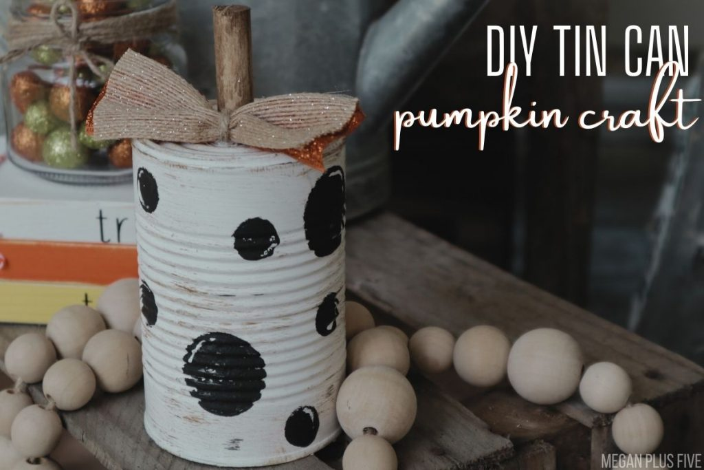 tutorial showing you how to make tin can pumpkins. White painted tin can with black polka dots. Burlap & orange bow and dowel rod stem are on the top of the metal can pumpkin. Natural bead garland drapes around the fall pumpkin craft