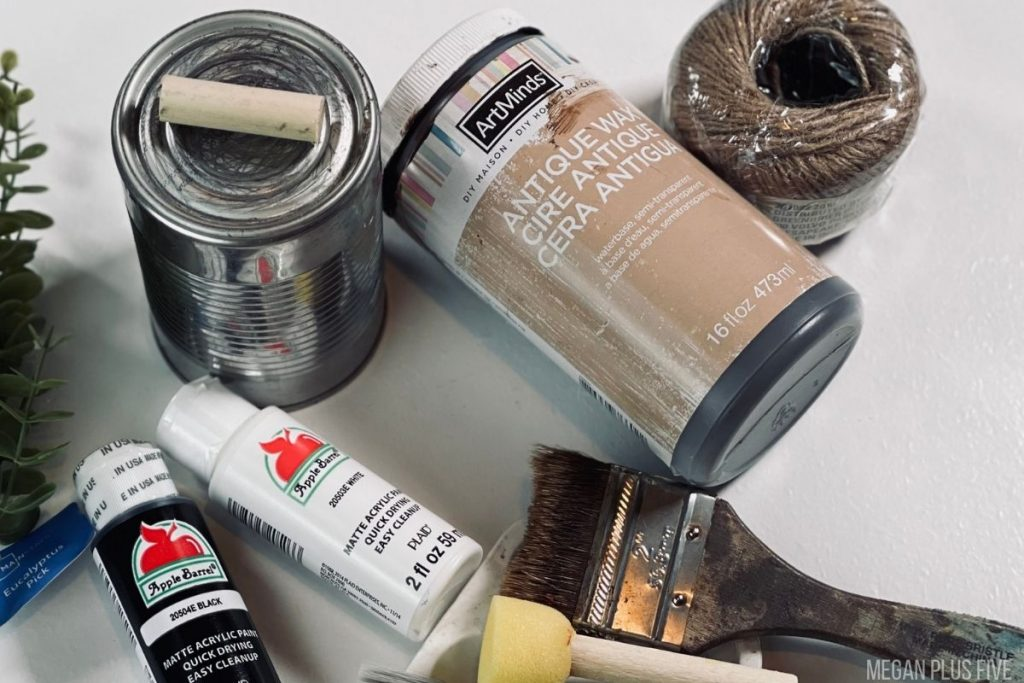 supplies and materials to make a tin can pumpkin. Metal tin can, black and white acrylic paint, antiquing wax, paint brush, round sponge dabber brush, chip brush, twine